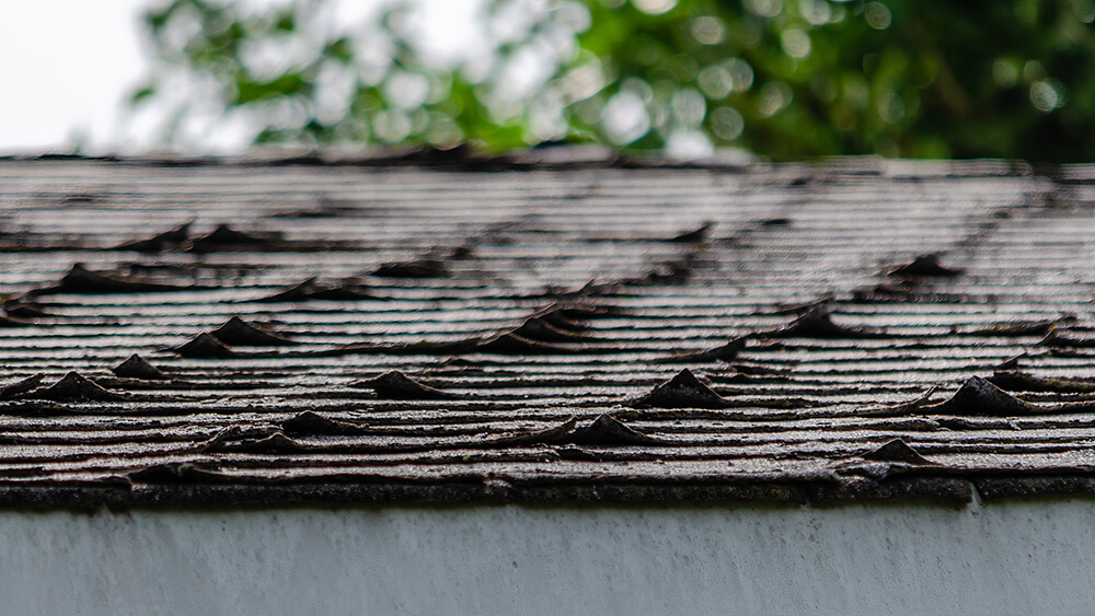 Close-up of curled roofing shingles on a residential rooftop