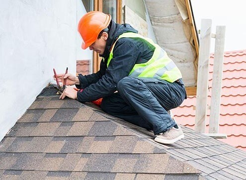 man installing shingles on a roof