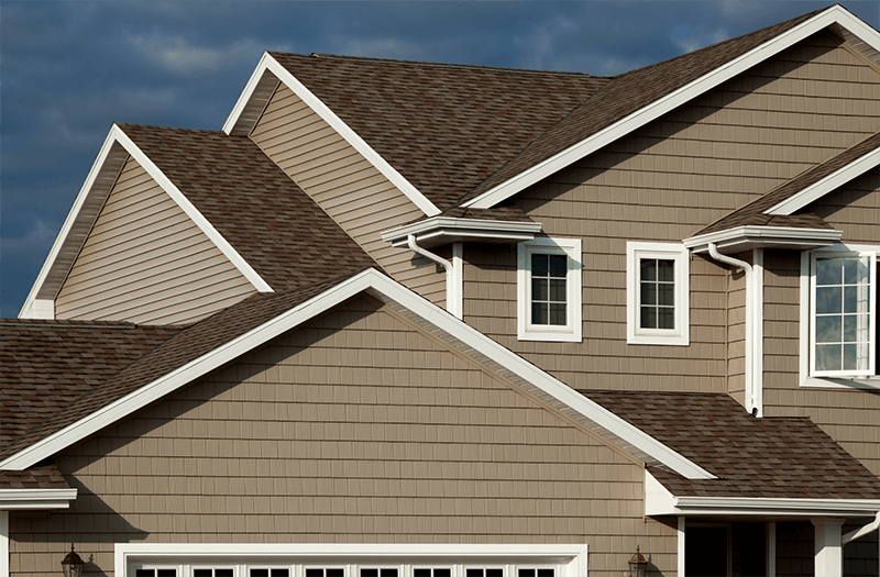 Residential home with complex roof sections covered with brown, textured asphalt shingles.